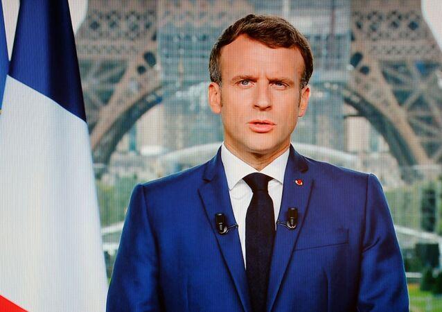 Presidente francês Emmanuel Macron é visto em uma tela de televisão durante discurso transmitido à nação em Paris em 12 de julho de 2021