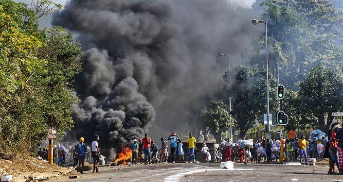 Manifestantes no exterior de centro comercial e perto de barricada em chamas em Durban, África do Sul, 12 de julho de 2021
