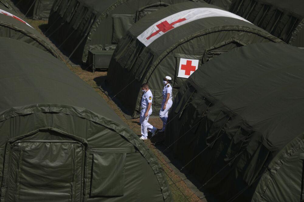 Oficias navais caminham entre as tendas durante o exercício militar antes da inspeção da ONU