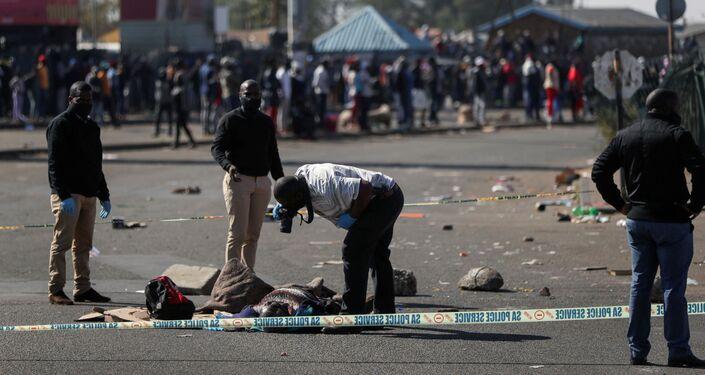 Policiais inspecionam o corpo de uma vítima em meio aos protestos em Katlehong, África do Sul, 12 de julho de 2021