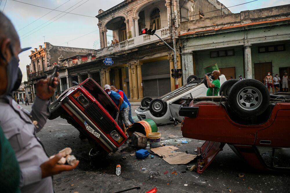 Viaturas policias e veículos civis foram vistos capotados na rua durante a manifestação contra o presidente cubano Miguel Diaz-Canel em Havana, no domingo (11)