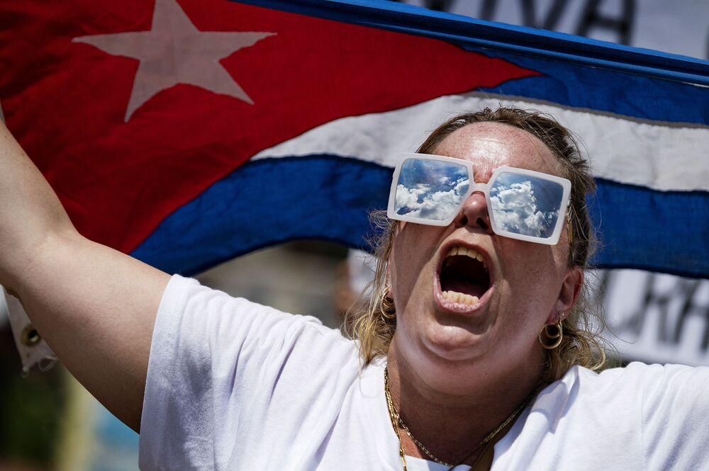 Uma manifestante segura a bandeira cubana enquanto protestava em frente à Casa Branca, em Washington, nos EUA, na segunda-feira (12)