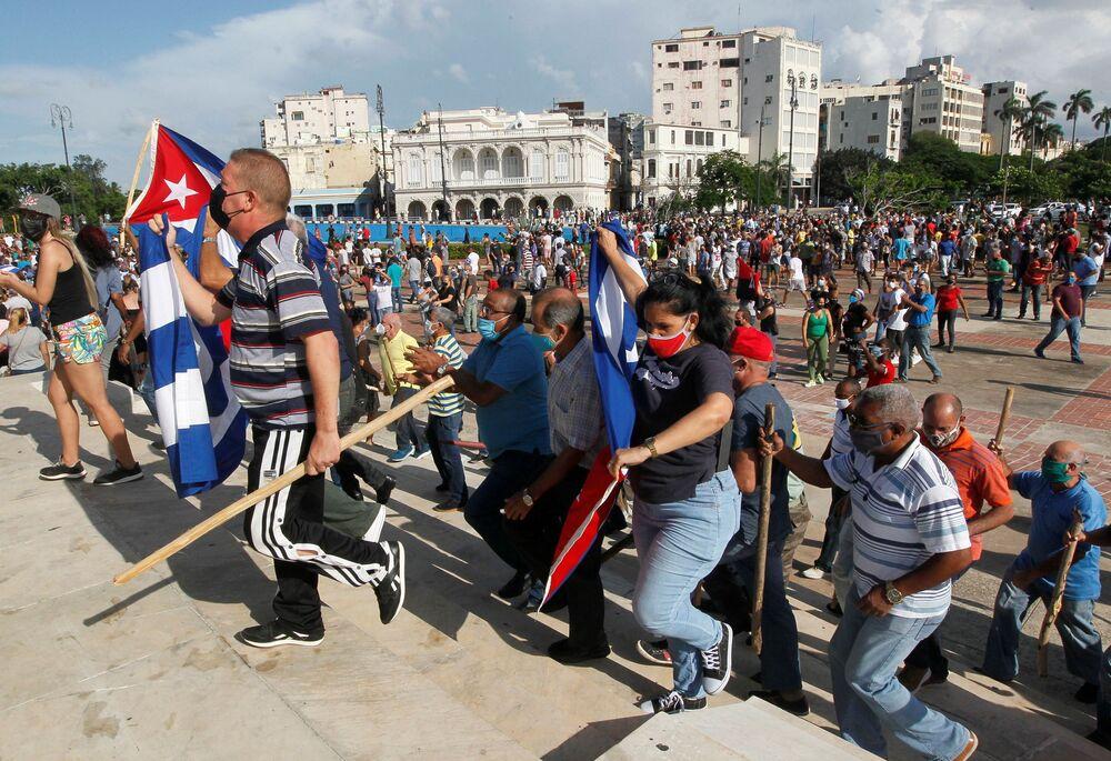 Apoiadores do governo caminham durante protestos contra e em apoio ao governo, em meio ao surto da COVID-19, em Havana, no domingo (11)