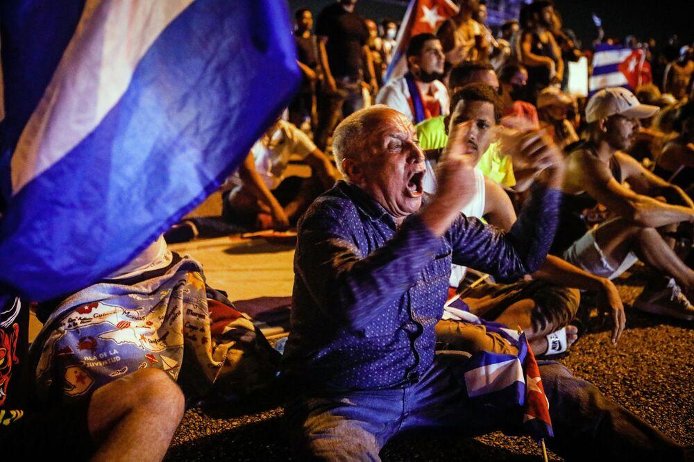 Um homem grita enquanto pessoas bloqueiam a via expressa Palmetto durante a manifestação em apoio aos cubanos, em Miami, na terça-feira (13). Uma pessoa morreu e mais de 100, incluindo jornalistas independentes e dissidentes, foram presas após o ato inédito em Cuba