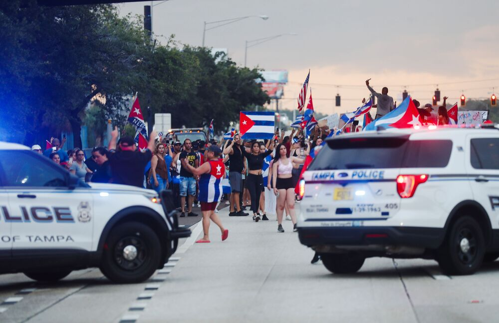 Veículos da polícia de Tampa, na Flórida, são bloqueados por manifestantes em uma estrada durante protesto contra o governo cubano, na terça-feira (13)