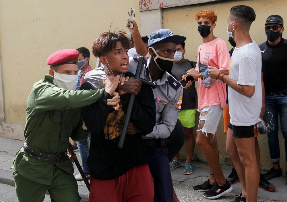 Policiais imobilizam uma pessoa durante os protestos contra e em apoio ao governo, em Havana, no domingo (11)