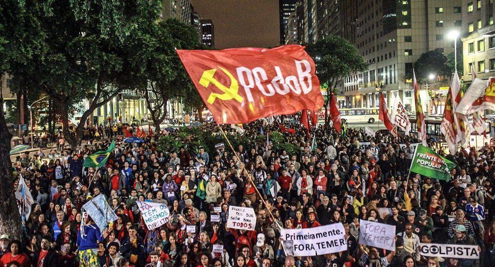 Bandeira do PCdoB durante manifestação. Segundo analista, esses partidos são bons para manutenção de partidos mais ideológicos do que fisiológicos no Brasil
