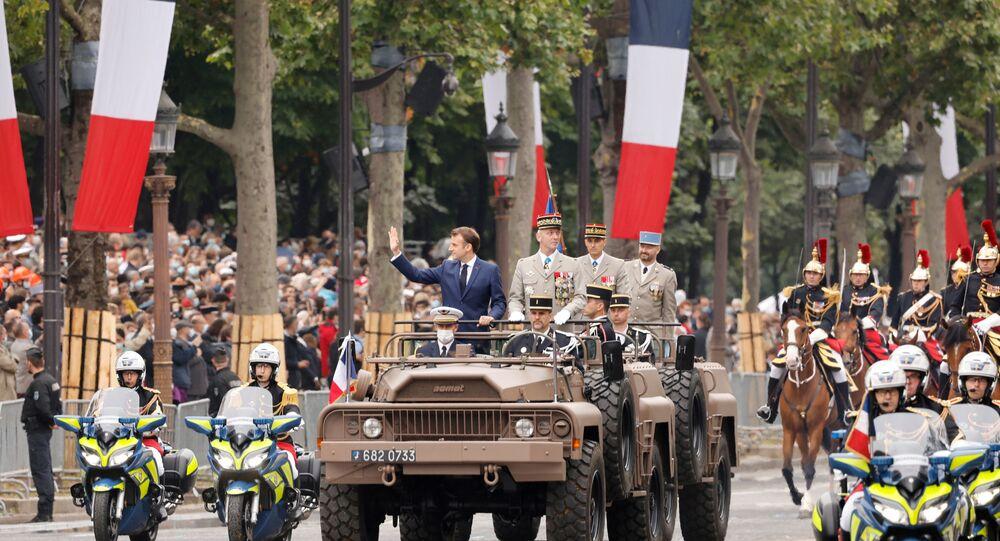 Presidente francês Emmanuel Macron e chefe das Forças Armadas da França, general François Lecointre, de pé no carro de comando para inspecionar tropas durante celebrações de 14 de julho na França, 14 de julho de 2021