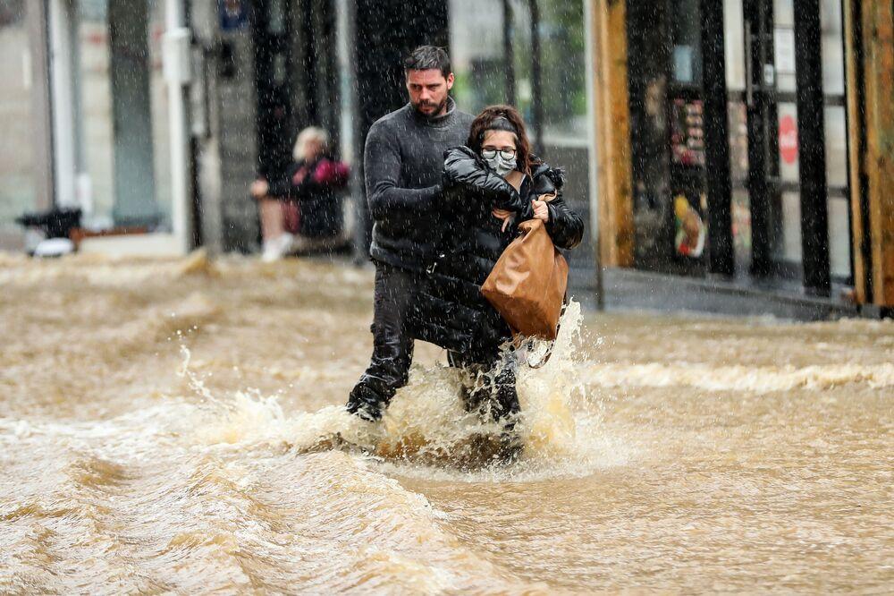 Homem ajuda mulher a atravessar rua inundada na cidade de Spa, na Bélgica
