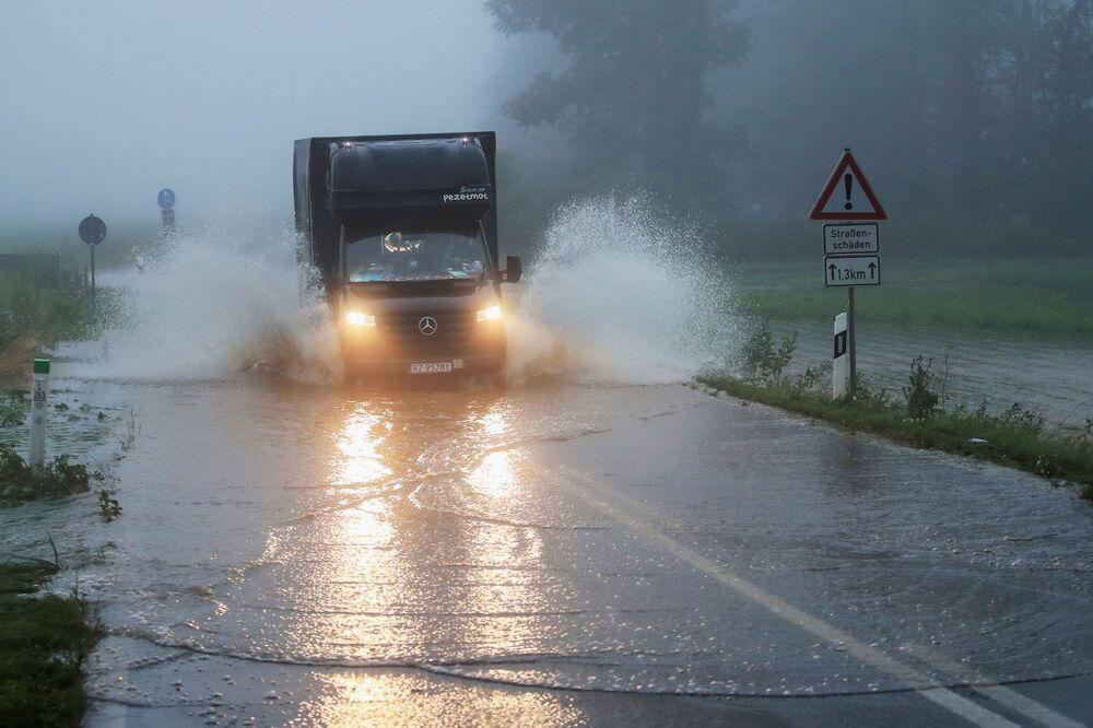 Carro passa em estrada atingida por enchentes na Alemanha