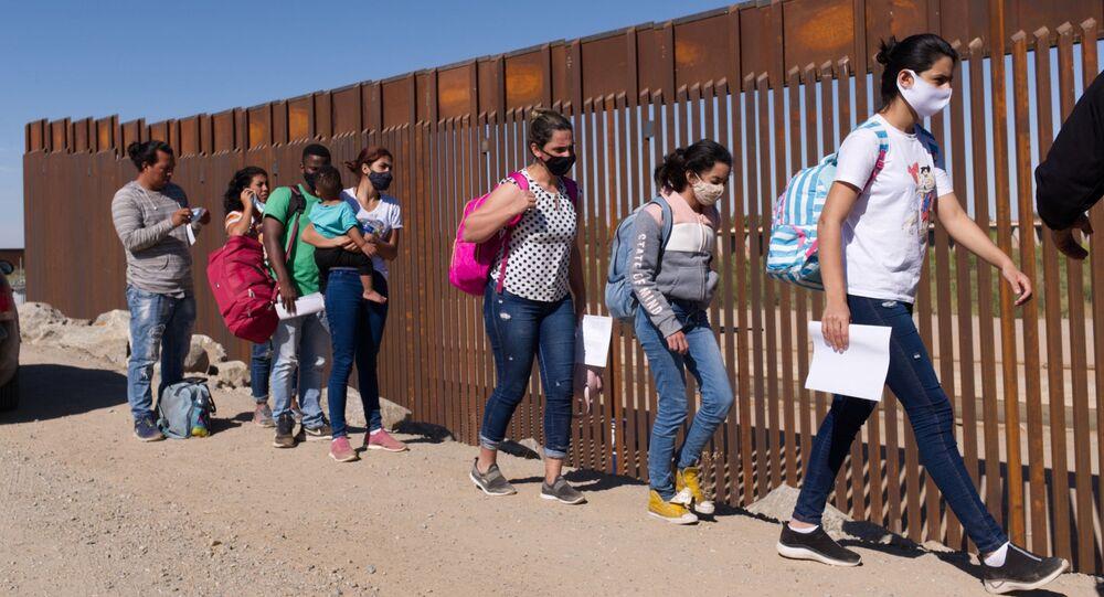 Um grupo de migrantes brasileiros contorna uma lacuna na fronteira dos EUA com o México em Yuma, Arizona, buscando asilo nos Estados Unidos após cruzar o território do México, 8 de junho de 2021