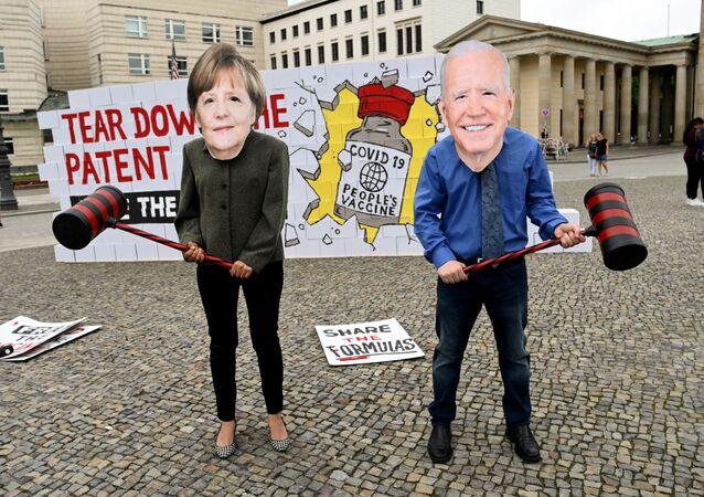 Manifestantes disfarçados da chanceler alemã Angela Merkel e presidente americano Joe Biden se preparam para destruir o muro de patentes em frente do Portão de Brandemburgo, Berlim, Alemanha, 14 de julho de 2021