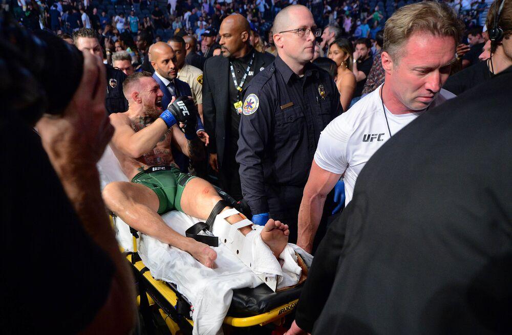 Lutador irlandês Conor McGregor é levado em maca após combate com o lutador dos EUA Dustin Poirier