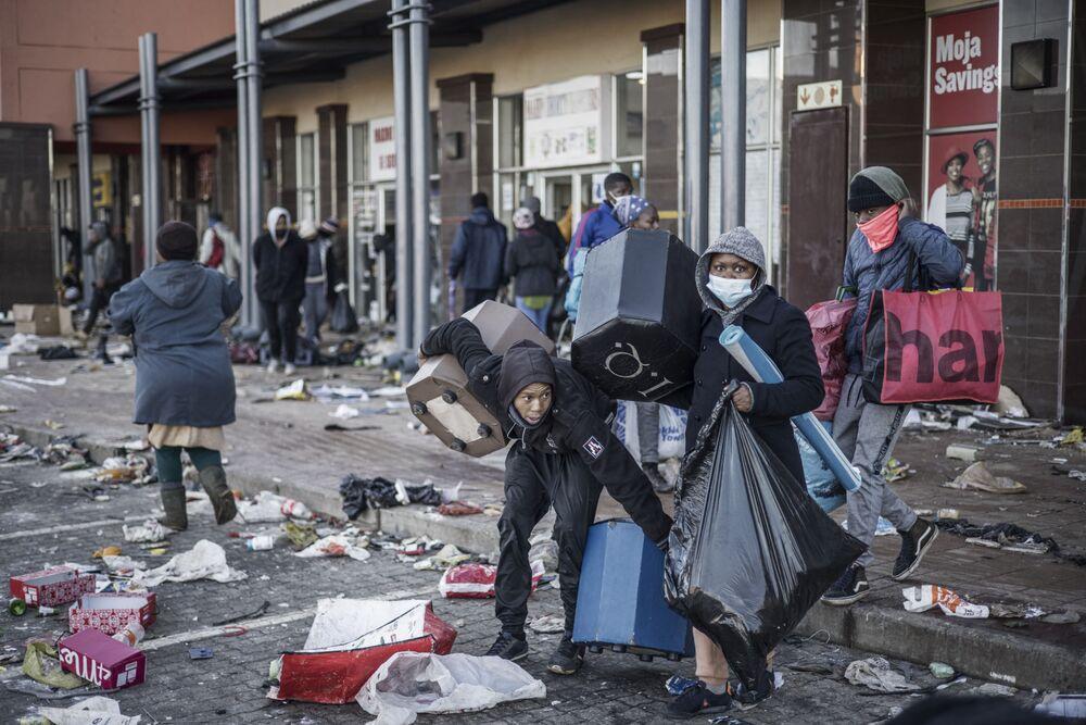 Saqueadores roubam produtos de um centro comercial em Vosloorus, África do Sul