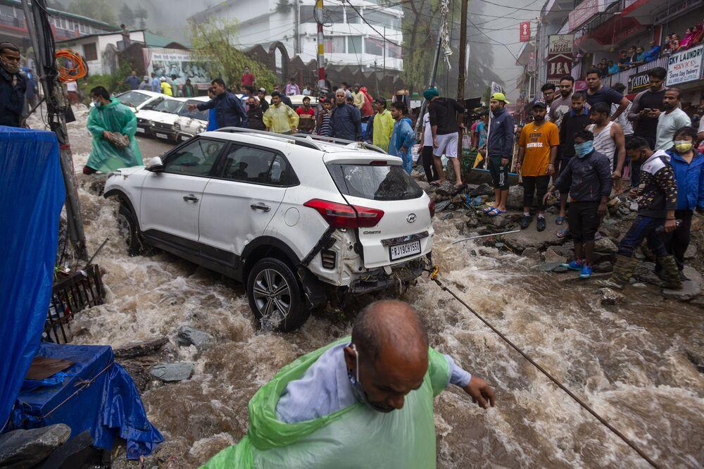 Pessoas tentam recuperar carro danificado nas inundações provocadas pelas chuvas torrenciais na Índia
