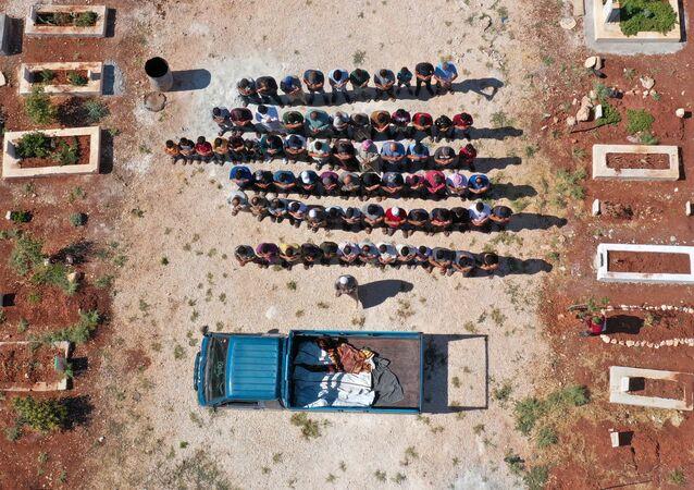 Vista aérea mostra enlutados orando pelos corpos de três crianças, que foram mortas em um bombardeio na província de Idlib, no noroeste da Síria