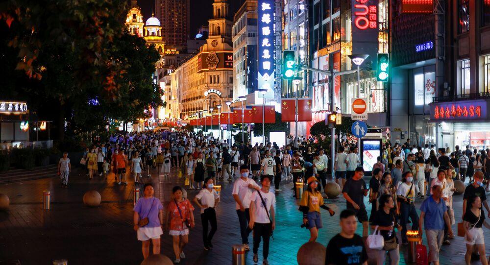 Pessoas na principal zona comercial de Xangai, China, 12 de julho de 2021