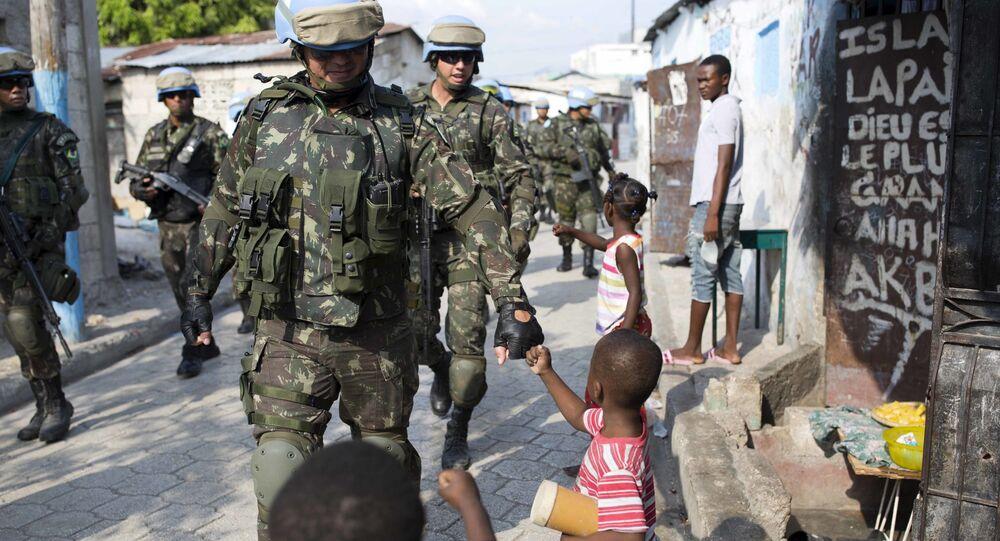 Soldados da paz da ONU do Brasil com crianças enquanto patrulham a favela Cite Soleil, em Porto Príncipe, Haiti., 22 de fevereiro de 2017