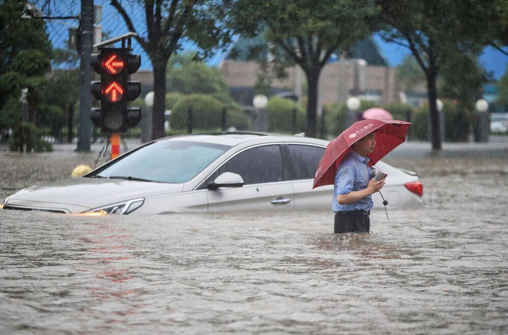 Homem ao lado de carro sumerso em Zhengzhou, província de Henan, China, 20 de julho de 2021