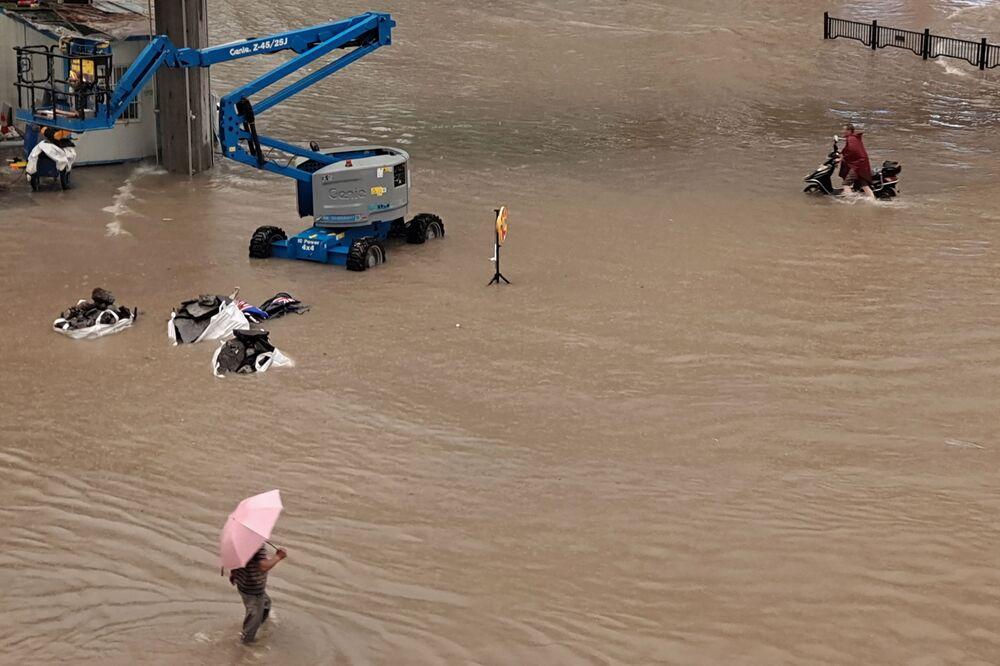 Pessoas passam por rua inundada após as chuvas torrenciais que atingiram a cidade de Zhengzhou, China, 20 de julho de 2021