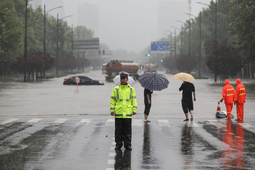 Policial em frente de rua inundada em Zhengzhou, província de Henan, China, 20 de julho de 2021