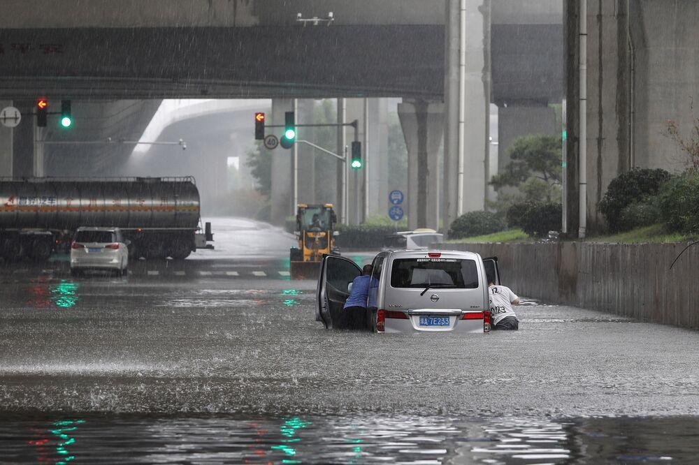 Pessoas empurram uma furgoneta durante as chuvas fortes que atingiram a cidade de Zhengzhou, China, 20 de julho de 2021