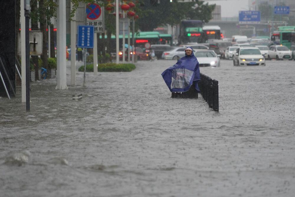 Mulher usando capa de chuva em estrada inundada na cidade de Zhengzhou, China, 20 de julho de 2021