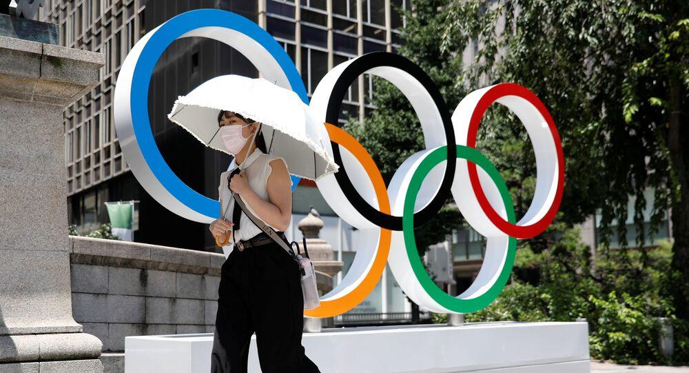 Mulher passa pelo símbolo dos Jogos Olímpicos em Tóquio, antes do começo da competição, 21 de julho de 2021