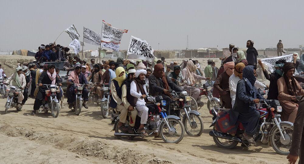 Apoiadores do Talibã carregam andeiras brancas do grupo na cidade de Chaman, fronteira entre o Afeganistão e o Paquistão, 14 de julho de 2021
