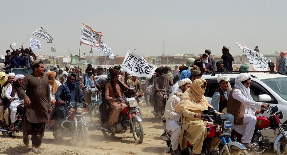 Pessoas com bandeiras do Talibã se movendo para o Portão da Amizade, posto de passagem na fronteira entre Paquistão e Afeganistão, cidade de Chaman, Paquistão, 14 de julho de 2021