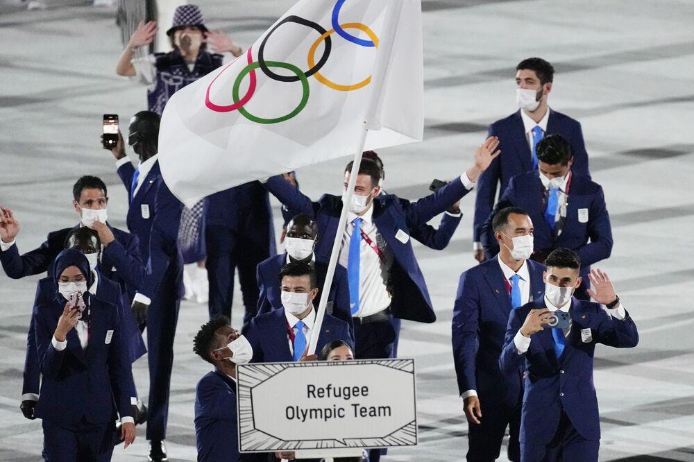 Yusra Mardini e Tachlowini Gabriyesos, da Seleção Olímpica de Refugiados, carregam a bandeira olímpica durante a cerimônia de abertura nesta sexta-feira (23), em Tóquio, Japão