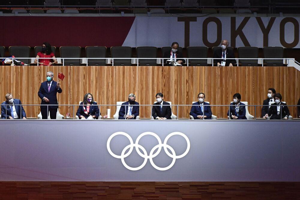 O membro do Comitê Olímpico Internacional (COI), Zaiqing Yu (2º à esquerda), gesticula para o vice-presidente do COI John Coates, membro do COI, Anita DeFrantz, o presidente do COI Thomas Bach e o imperador do Japão Naruhito (3º à esquerda) na cerimônia de abertura dos Jogos Olímpicos de Tóquio 2020