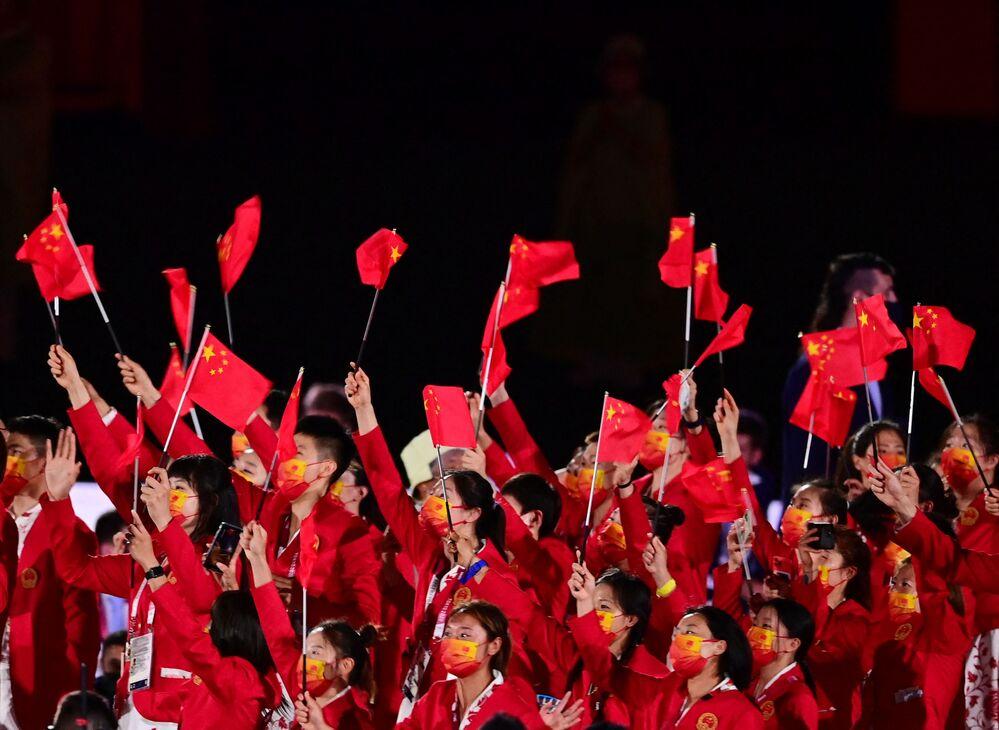 Atletas da delegação da China agitam bandeiras ao entrar no Estádio Olímpico durante a cerimônia de abertura dos Jogos Olímpicos de Tóquio 2020