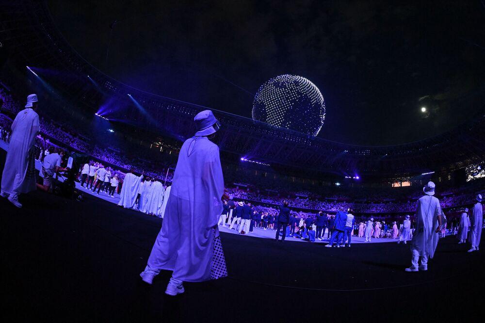 Atletas e voluntários assistem a drones voando para formar um globo no céu sobre o Estádio Olímpico durante a cerimônia de abertura dos Jogos Olímpicos de Tóquio 2020