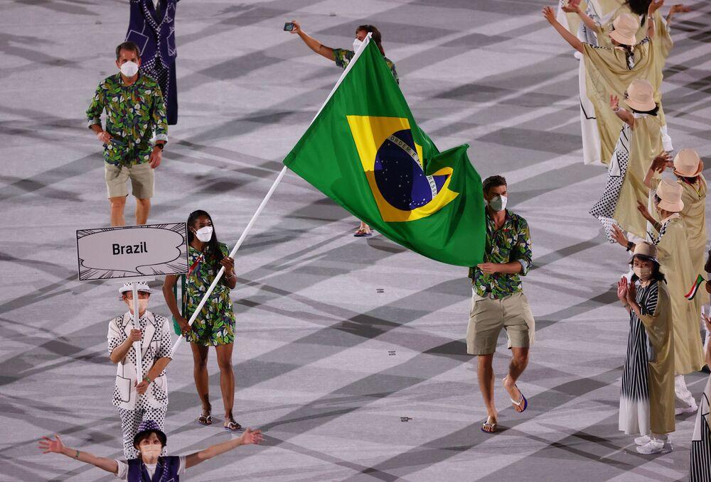 Os atletas brasileiros Ketleyn Quadros e Renato Rezende levam a bandeira do país durante o desfile de atletas na cerimônia de abertura dos Jogos de Tóquio 2020, nesta sexta-feira (23)
