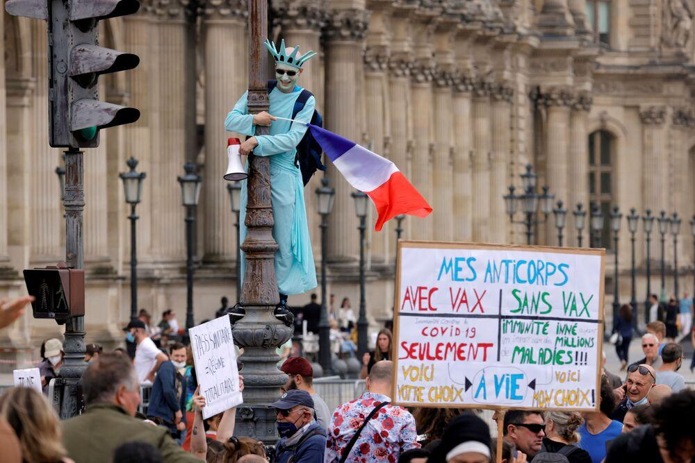 Manifestante fantasiado da Estátua da Liberdade participa dos protestos contra as novas medidas anunciadas pelo presidente francês Emmanuel Macron para combater a COVID-19, em Paris, França, 17 de julho de 2021