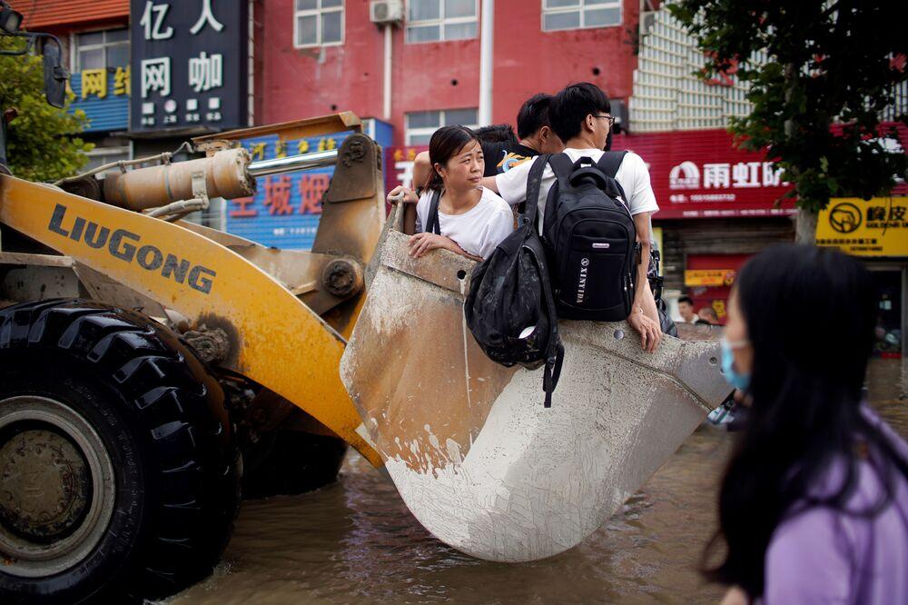 Pessoas viajando em uma carregadeira devido às estradas inundadas após chuvas fortes em Zhengzhou, província de Henan, China, 22 de julho de 2021