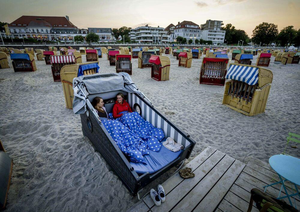Duas moças se preparam para passar a noite em uma cadeira da praia especialmente projetada, na costa do mar Báltico, Alemanha, 18 de julho de 2021