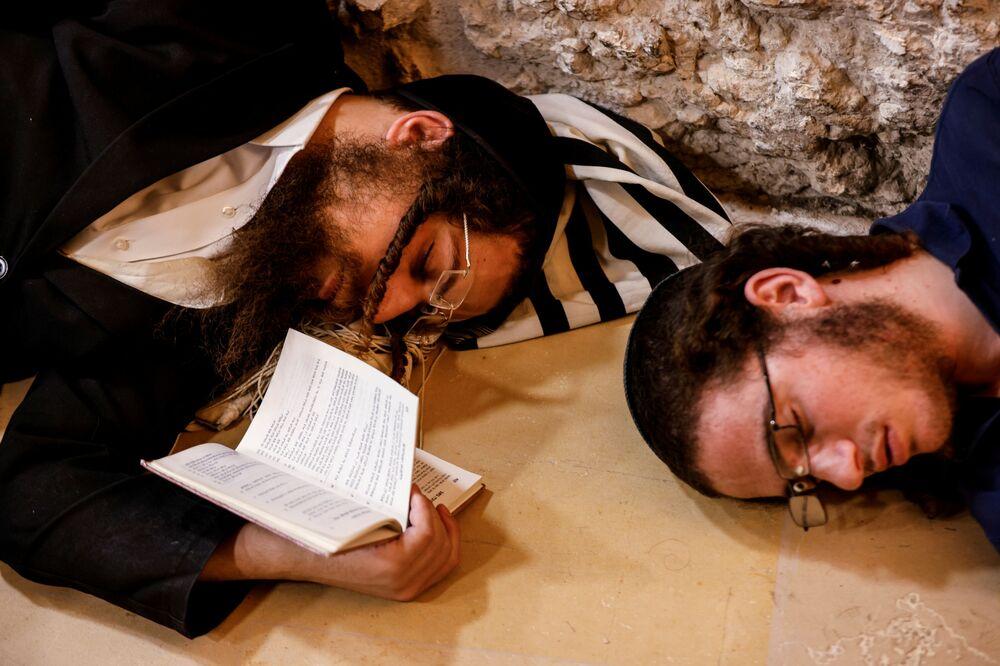 Fiéis judeus dormem durante o Tishá BeAv, o dia de luto para comemorar a destruição do Primeiro e Segundo Templos de Jerusalém, Israel, 18 de julho de 2021