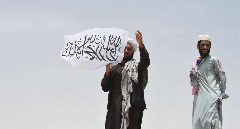 Homem no lado afegão da fronteira segura uma bandeira do Talibã, no Afeganistão