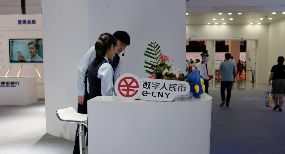 Pessoas ao lado do símbolo do yuan digital em Xangai, China, 8 de julho de 2021