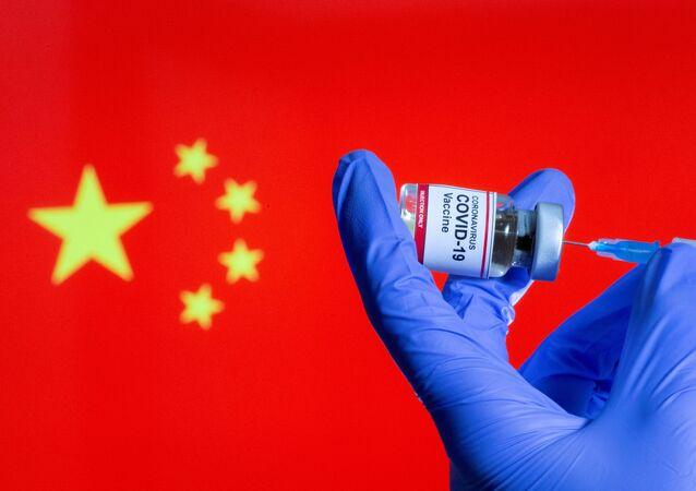 Uma pessoa segura um frasco de vacina contra COVID-19 em frente à bandeira da China