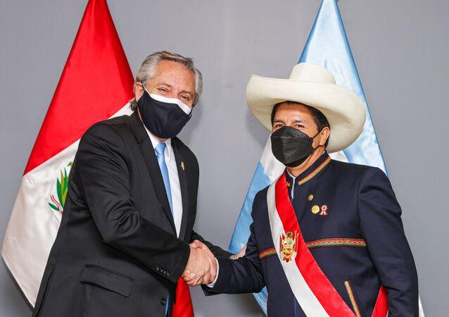 Novo presidente do Peru Pedro Castillo (à direita) e presidente da Argentina Alberto Fernández apertam mãos durante cerimônia de posse em Lima, 28 de julho de 2021