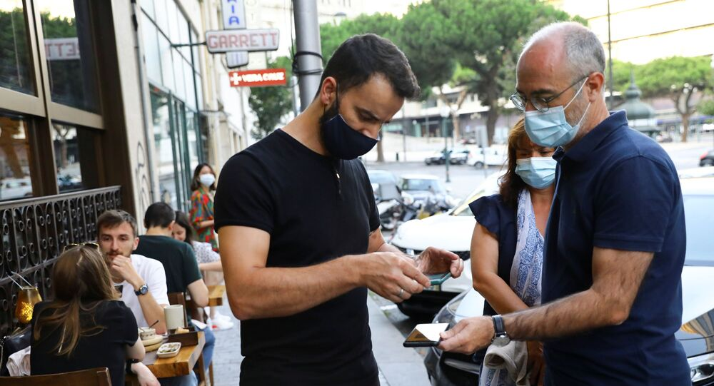 Funcionário de restaurante checa o certificado digital de vacinação no Porto, no norte de Portugal, em 10 de julho de 2021