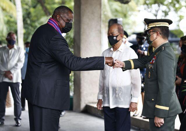 Secretário de Defesa dos EUA Lloyd Austin (à esquerda) saúda o chefe do Estado-Maior das Forças Armadas das Filipinas, general Cirilito Sobejana (à direita) e o ministro da Defesa filipino Delfin Lorenzana (no centro), Manila, 30 de julho de 2021