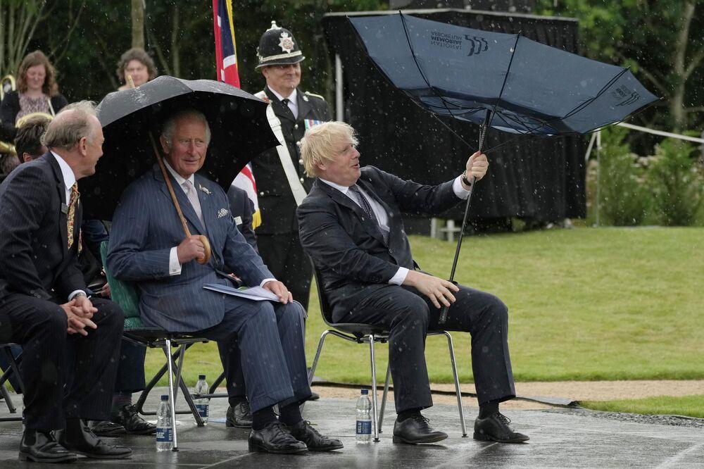 Charles, príncipe de Gales, e o primeiro-ministro britânico, Boris Johnson, se abrigam de chuva em Alrewas, Reino Unido, 28 de julho de 2021