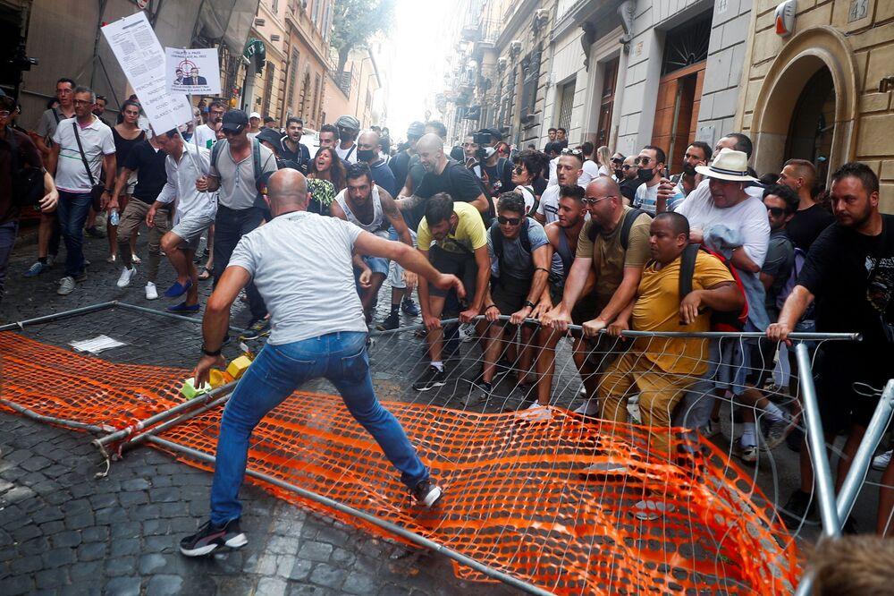 Manifestantes removem barreiras colocadas pela polícia durante protestos contra os certificados de COVID-19, Roma, Itália, 27 de julho de 2021