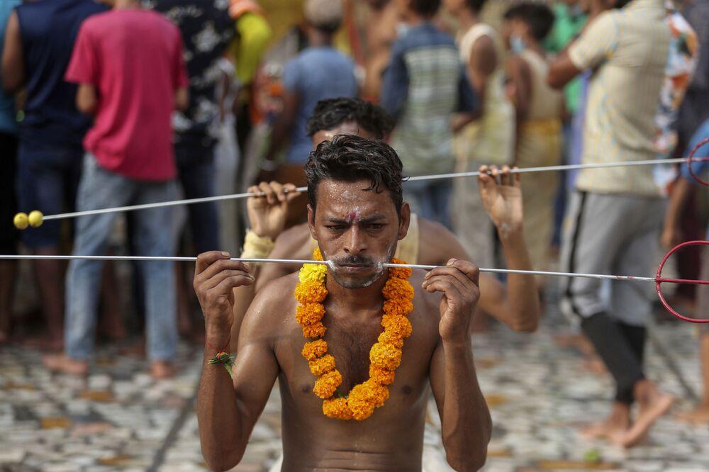 Fiéis com tridente de aço perfurando suas faces como parte de um ritual,  no templo da deusa hindu Sheetla Mata em Jammu, Índia, 25 de julho de 2021