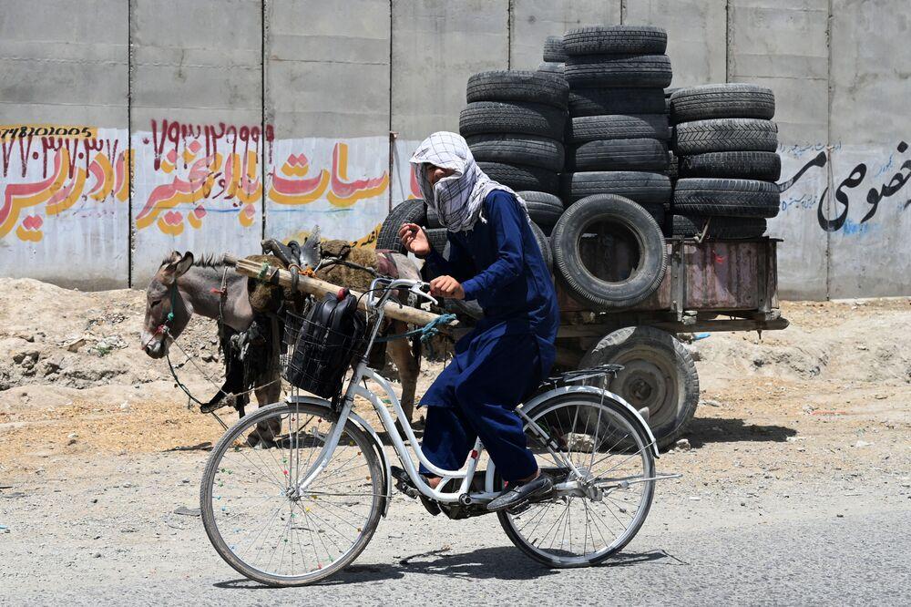Jovem andando de bicicleta em Cabul, Afeganistão, 27 de julho de 2021