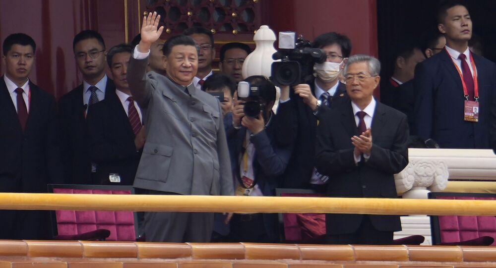 O presidente chinês, Xi Jinping, ao centro, acena ao lado do ex-presidente Hu Jintao, à direita, durante cerimônia para marcar o 100º aniversário da fundação do Partido Comunista Chinês em Pequim, em 1 de julho de 2021